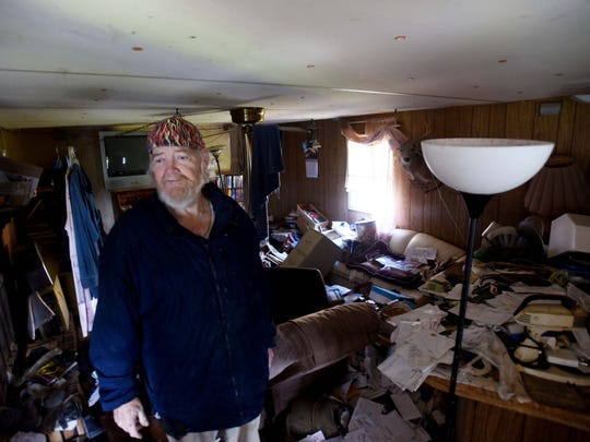 David Rogers stands in his mobile home that was destroyed