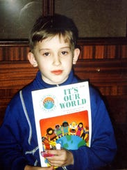 A boy in Belarus holds a coloring book that was a gift