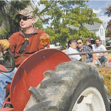 Greg Buell drives the tractor pulling a haybale-seat trailer with Barbara Krueger giving information about the village of Hartland during 2012's Hartland Heritage Day. This year's heritage celebration is set for Saturday.