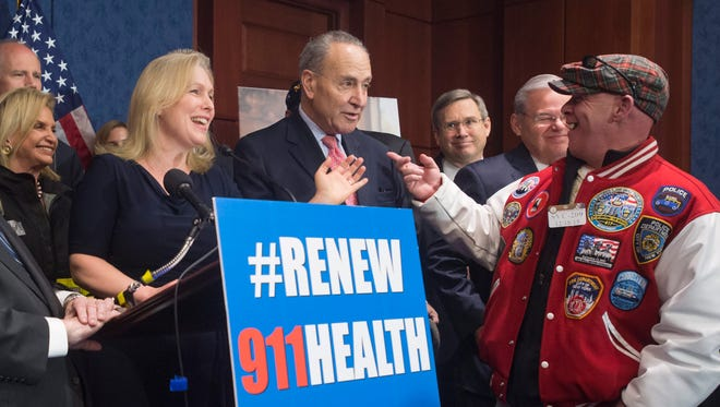 Democratic New York Sens. Kirsten Gillibrand (front, left) and Chuck Schumer (center) share a laugh with activist John Feal (front right) during a news conference to celebrate the passage of the James Zadroga 9/11 Health and Compensation Reauthorization Act, on Dec. 18, 2015 on Capitol Hill in Washington, D.C.