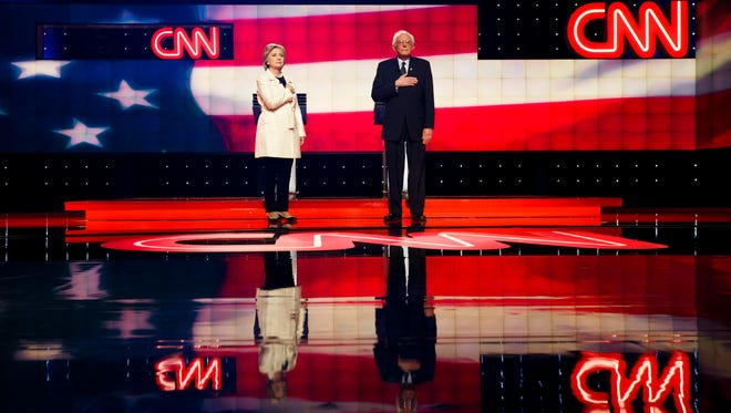 Hillary Clinton and Bernie Sanders appear on stage during the start of a CNN-sponsored debate in Brooklyn on April 14, 2016.