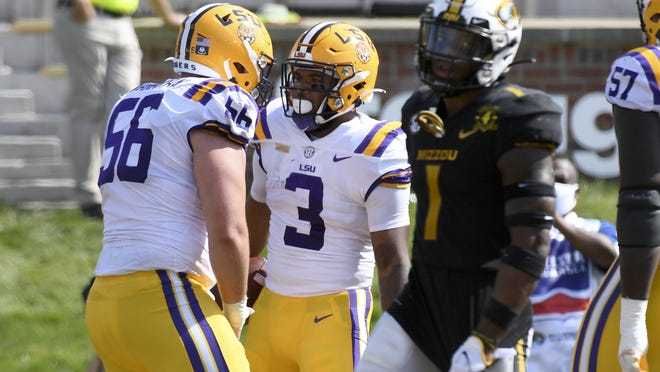 LSU running back Tyrion Davis-Price (3) is congratulated by teammate Liam Shanahan (left) after running for a touchdown during the second half of an NCAA college football game on Oct. 10, 2020, in Columbia, Mo.