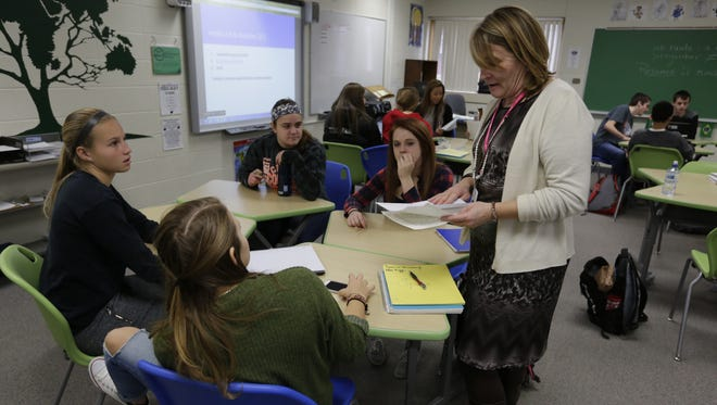 Kathy Heinen looks over some work done by the Global Academy students that were learning Spanish vocabulary during class at Oshkosh West High School.