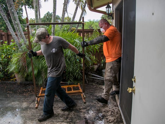 Philip Lyman and his father John remove a bedframe from Jan Erickson's flooded condo in Royal Woods on Saturday, September 2, 2017. The Lymans and lots of other volunteers from Next Level Church worked all over the neighborhood to help residents clear out to prepare for the cleaning and rebuilding process.