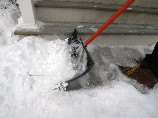 Bob Moore, a quarterback on the team, pushes fluffy snow from a sidewalk in West York on Wednesday. Team members were hard at work both Tuesday and Wednesday, donating their labor services.
