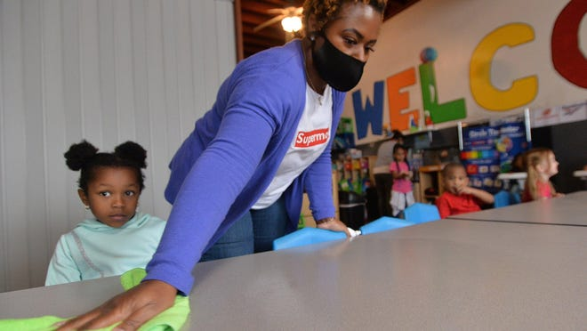 Learning Ladder Early Child Care co-owner Kenya Johnson cleans tables as children gather to eat Wednesday afternoon.