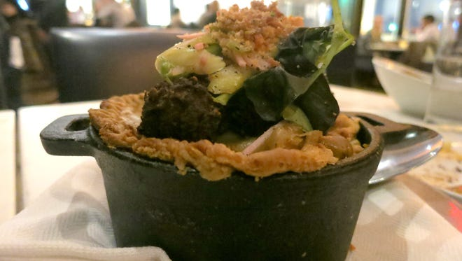 Served in an individual iron pot, rabbit pot pie is topped with pork-belly pepper dumplings, fresh greens and breadcrumbs at Republic restaurant in Detroit.