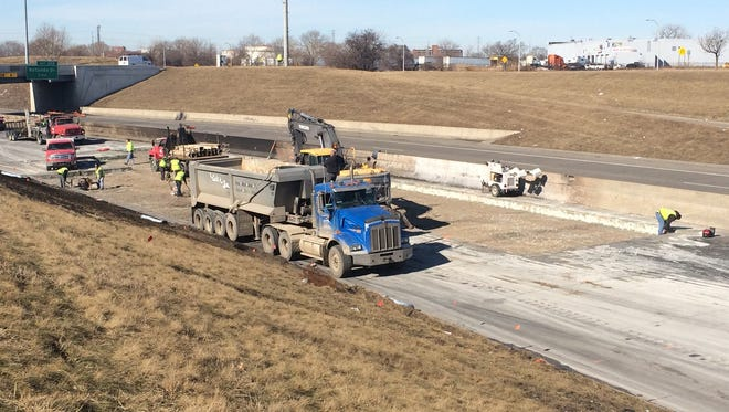 Crews cut out a large section of pavement from eastbound I-94 on Thursday, March 12, 2015 after a fuel tanker carrying 13,000 gallons exploded into multiple fireballs on Wednesday, March 11, 2015, on the border of Dearborn and Detroit.