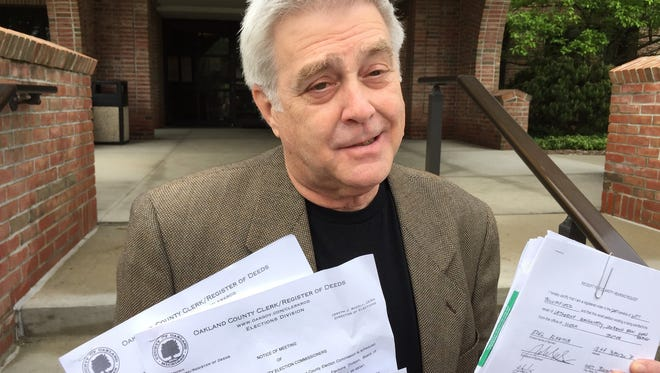 West Bloomfield Township Trustee Larry Brown stands outside the township hall Saturday, May 16, 2015, holding up some of the six recall petitions filed against him in the last five years, none of which has gotten onto an election ballot. Michigan is one of the top states for having a high volume of recalls and recall attempts, according to a recent study. Bill Laitner/Detroit Free Pres