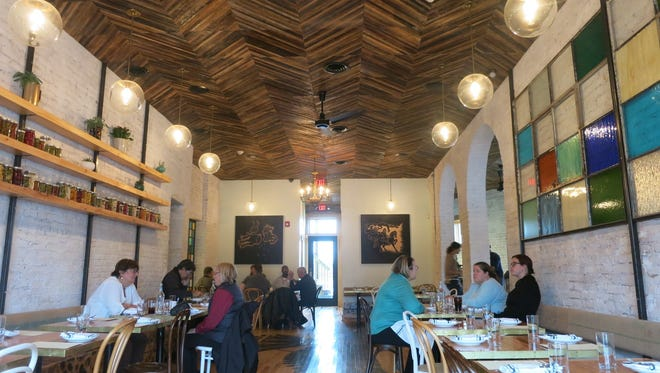 The Gold Cash Gold dining room is decorated simply with stained glass panels built with salvaged warehouse windows, a ceiling made of reclaimed wooden lathe from the restaurant's old walls, and shelves holding cans of the chef's homemade pickles.