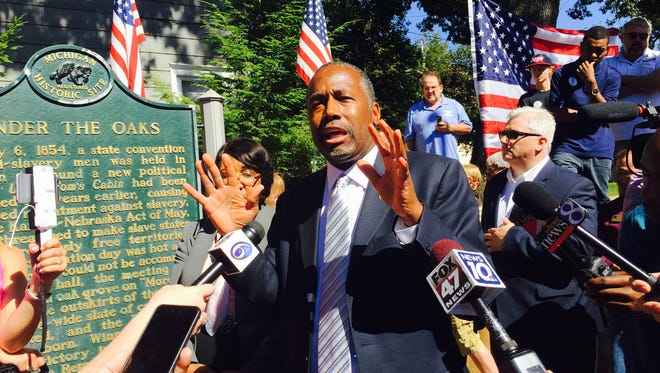 Dr. Ben Carson, Detroit native and Republican candidate for president, is photographed with the historical marker, Under the Oaks, the birthplace of the Republican party in Jackson on Sept. 23, 2015.