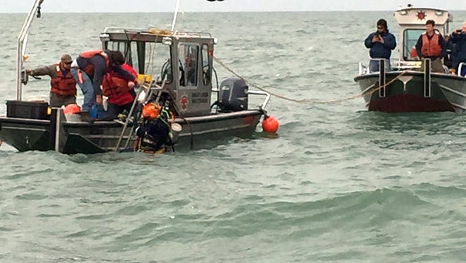 Contractors conduct dive operations at the site of a sunken barge near the Kelleys Island Shoal in Lake Erie, Oct. 21, 2015.  The divers were trying to establish the identity of the barge and if it or any of its cargo poses an environmental threat.