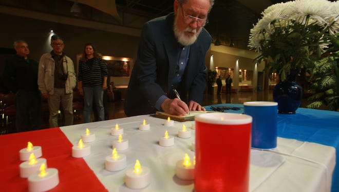El Paso Community College government Professor Leon Blevins on Friday night at the El Paso Community College Administrative Service Center signs a book of condolences that will be sent to Paris.