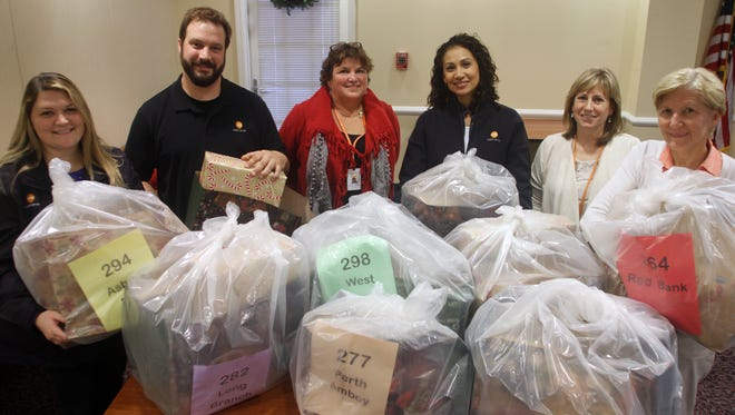 From left: Social worker Meghan Gilburn, Ted Giannechini, facilities coordinator, Pauline DePalma, manager of volunteers, Denise Andino nurse supervisor, Lisa Karew, coordinator of volunteers, and volunteer Brenda Ward, with gifts for needy families, Tuesday, Dec. 1, 2015, at the Visiting Nurse Association of Central New Jersey in Red Bank.