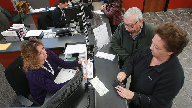 Vehicle Registration Clerk Ruth Sierra, left, assists Gloria and Arturo Chacon, who were renewing their vehicle registration last year at the El Paso County Tax Assessor-Collector office at 301 Manny Martinez Drive. A kiosk at the office will accept child support payments and court-ordered fees.
