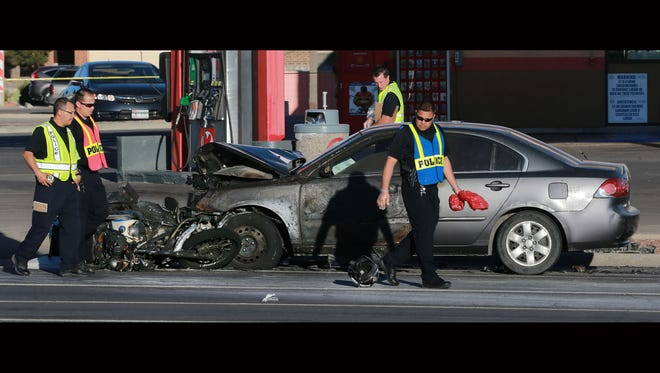 El Paso police investigate a traffic accident in which a police officer's motorcycle was rear-ended by a car Thursday on Lee Treviño Drive at Vista Del Sol Drive. The officer's cycle is at the front of the car.