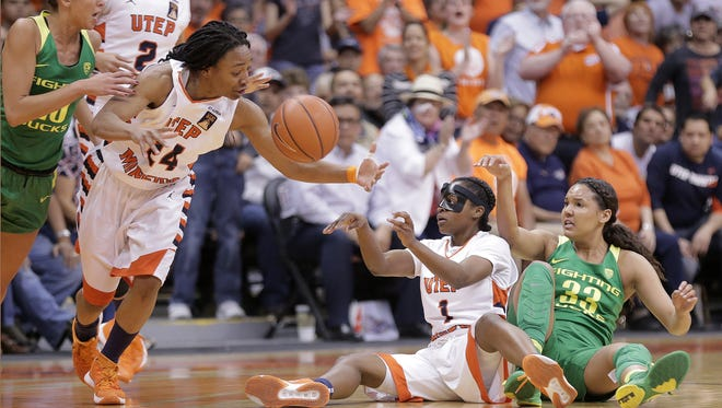 UTEP's Starr Breedlove passes to teammate Jenzel Nash from the floor after diving for a loose ball against Oregon's Lexi Petersen Monday at the Don Haskins Center. UTEP lost their WNIT quarterfinal game 71-67.