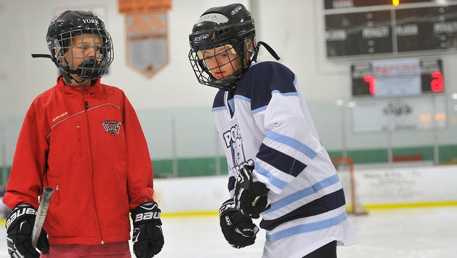 Caleb Olver, left, a mentor with the York Devils hockey team,  helps Adam Bernhardt, 12,  with his skating skills during practice for the York Polar Bears hockey team at the York city Ice Arena on Monday, April 25, 2016.
