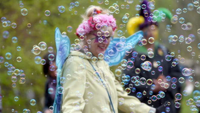 Sandy Prescott of Chicago, IL. is surrounded by bubbles during her visit toThe May Day Fairie Festival at Spoutwood Farm in Glen Rock on Friday, April 29, 2016.