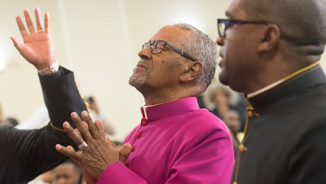 Carl H Scott joins members in prayer during his sacred service to become Bishop at the Bible Tabernacle Christian Center on Saturday, May 21, 2016.