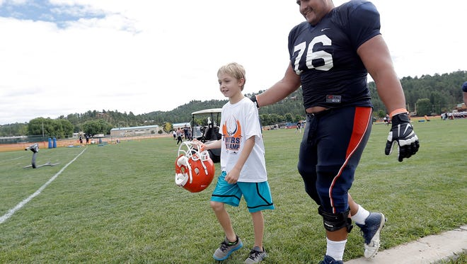 Will Hernandez, a UTEP offensive lineman, walks with a child from the Boys and Girls Club of Ruidoso after a practice in August 2016. Hernandez is expected to be a first- or second-round pick in the 2018 NFL Draft.