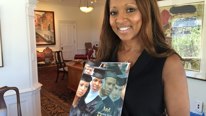 Jacqueline Wilson, wife of Wayne State University President Roy Wilson, founded the HIGH program to aid students in financial crisis.She stands in her office on 8/8/16 with a HIGH brochure.