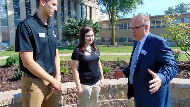 Dr. Chris E. Domes, president of Silver Lake College, far right, talks to students Luka Jovicic, left, and Ashley Rumlow during a day-long celebration launching SLC Works, its Work College model.