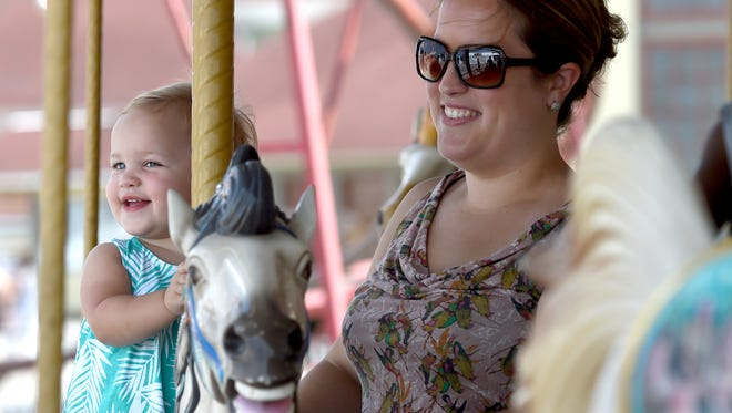 Gwendolyn Bastian is all smiles as she and her mother, Erin, see her dad, Alex, while riding the carousel at the York Fair. The 16-month-old has become a huge fan of carousels, as her parents have taken her on six different ones in the past four months.