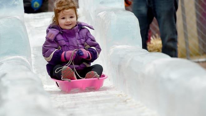 Josie Storey takes her turn riding a sled down the ice slide in Cherry Lane during the annual FestivICE event in downtown York on Saturday, Jan. 14, 2017.