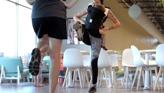 Ashley Kilday leads her prenatal/postnatal exercise class Wednesday at the westside Whole Foods with her daughter Norah, 1, strapped to her chest. The class allows mothers and children to exercise together while providing a support atmosphere for new and expecting moms.