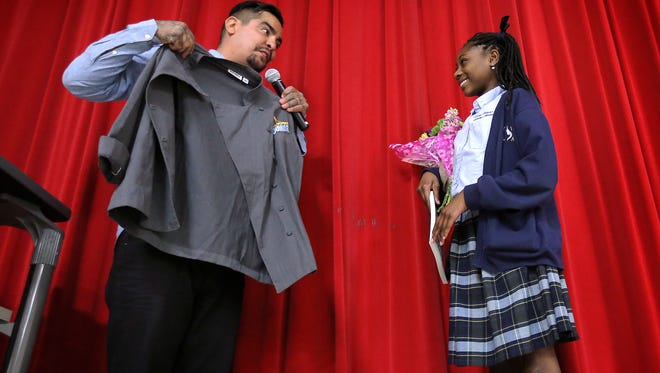 Celebrity Chef and El Pasoan Aaron Sanchez presents Young Women's Leadership Academy student Taliah Dancil with an official Chopped Jr. chef coat Tuesday during an assembly at her school. Dancil won Chopped Jr. last year.