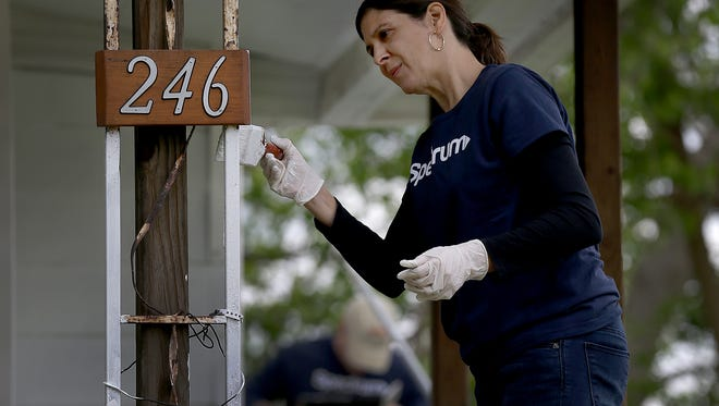 Desiree Deri, a volunteers from Charter Communication work on painting the home on the 200 hundred block of North Hamilton Ave.  Shepherd Community Center is looking to put 2,500 volunteers this summer on a project to repair 100 Near Eastside homes, rehab 25 more and build five new houses as part of an effort to break the cycle of poverty in its neighborhood.