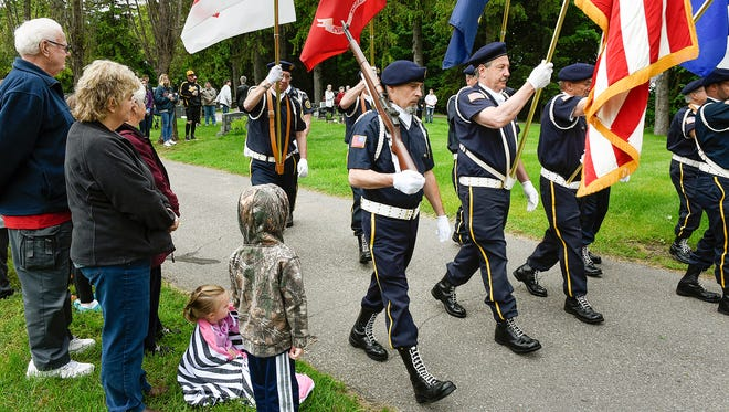 People watch as the color guard passes during a Memorial Day ceremony at the St. John's Abbey Cemetery May 2017, in Collegeville.