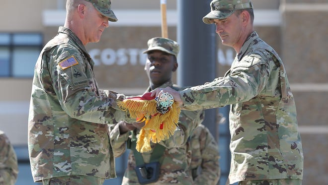 """Fort Bliss commanding general Maj. Gen. Robert """"Pat"""" White, left, and Division Command Sgt. Maj. Danny Day case the 1st Armored Division flag in preparation for their deployment to Iraq."""