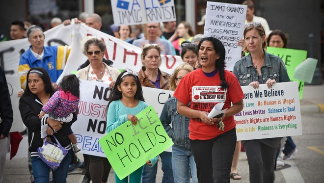 Maria Gutierrez leads people as they march around the Stearns County Courthouse Tuesday, Sept. 5, in St. Cloud during a rally in support of the Deferred Action for Children Arrivals program.