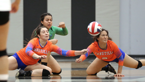 A trio of Canutillo volleyball players brace for impact