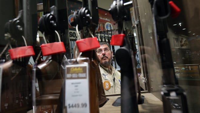 Rene Ramirez takes a shotgun from one of the many rifle cases at Cabela's.