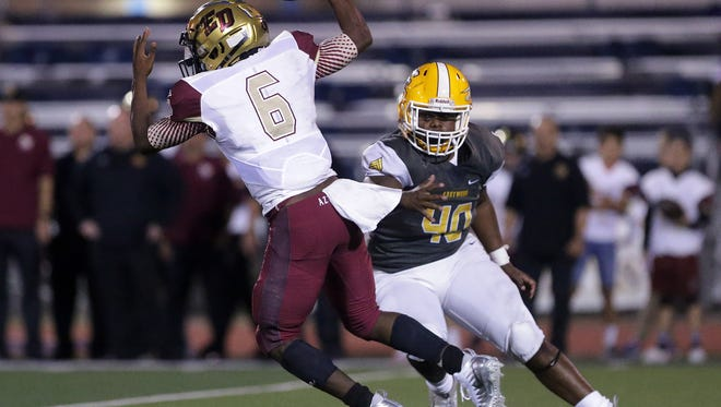 Eastwood defensive lineman Jamari Bullock chases El Dorado quarterback Cedarious Barfield out of the backfield in the first half of their game Friday at Eastwood High School.