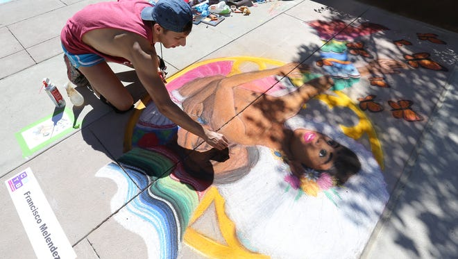 Francisco Melendez works on his chalk art during Chalk the Block in downtown El Paso Saturday.