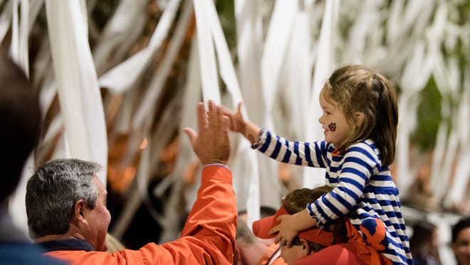 Cora Beth Brooks, 5, high fives her grandfather, David Brooks as they help roll Toomer's Corner after the NCAA football game between Auburn and Georgia on Saturday, Nov. 11, 2017, in Auburn, Ala. Auburn defeated Georgia 40-17.