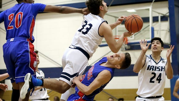 Cathedral's Franz Reyes tangles up with Las Cruces High's Ronald Brown, left, and Cayden Sherwood as he drives to the basket Tuesday night at Cathedral High School. Reyes was called for a charge on the play.