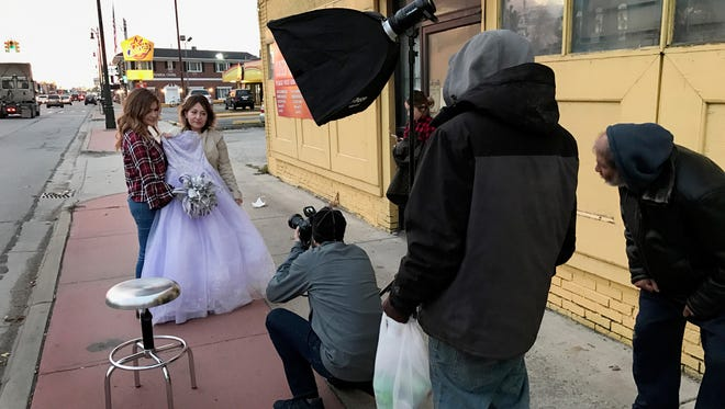 As two curious pedestrians look on Detroit Free Press photographer Romain Blanquart photographs Irene Guzman and her daughter Janet Guzman on Michigan Avenue in front of the now closed Fred Mora Portrait Studio where ten years ago they had Janet's Quinceanera portraits taken in Detroit on November 6, 2017.