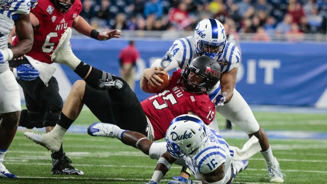 Northern Illinois QB (15) Marcus Childers is brought down by Duke defenders during the 2017 Quick Lane Bowl at Ford Field on Tuesday Dec. 26, 2017.