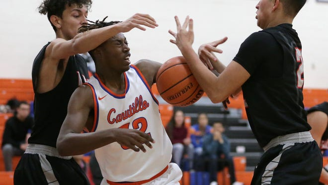 Canutillo's Tameron Stephney, center, takes a few fouls from Oscar Araiza, left, and Ernie Montoya, right, of Hanks in the first half of their game Friday at Canutillo High School.