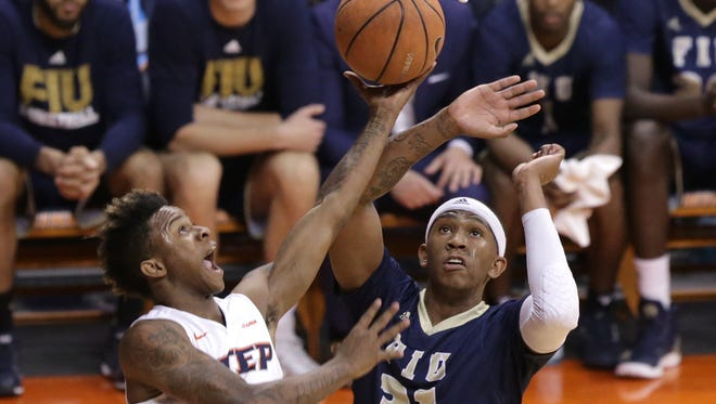 UTEP's Evan Gilyard shoots from behind the basket covered by FIU's Michael Douglas in the first half of their game Saturday at the Don Haskins Center.