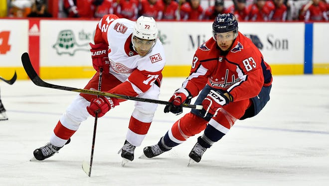 Red Wings left wing Andreas Athanasiou (72) and Capitals center Jay Beagle (83) chase the puck during the second period on Sunday, Feb. 11, 2018, in Washington.