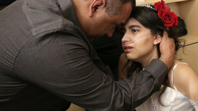 Lydia Dominguez shares a moment with her father after her wedding Monday at El Paso Children's Hospital. Dominguez decided to terminate treatment for her stage 4 renal cancer.
