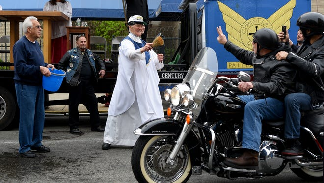 Father Mark Giordani blesses riders and their bikes at the end of the 49th annual Motorcycle Mass held on Main St. in Paterson on Sunday, May 6, 2018.  The event is sponsored by the Christian Riders Motorcycle Club founded Father Giordani in 1969.
