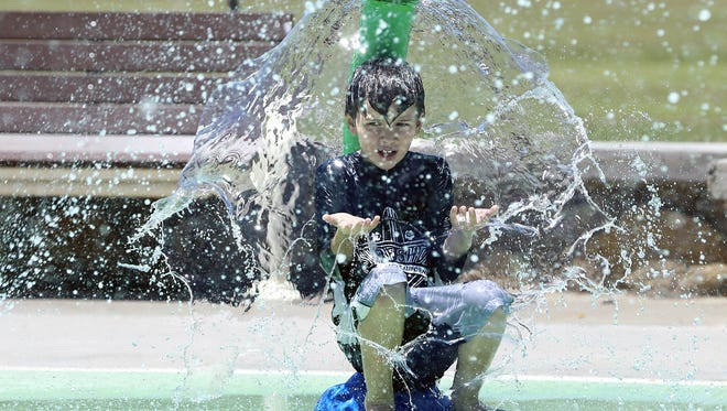 Eight-year-old Isaac Johnson rests under cascading water at the Sue Young Park splash pad in May as temperatures in El Paso neared triple digits.