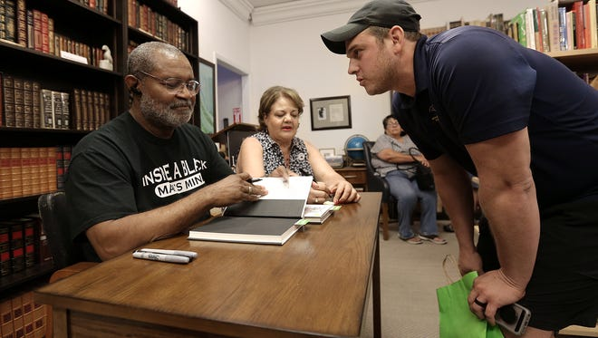 """Carlos Loweree III has his copy of """"Black Klansman"""" signed by author Ron Stallworth on July 14 at Literarity Book Shop in West El Paso."""